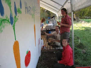 A perfect end-of-the season project:  Eli, Bill, Carolyn and Angelica painting the wall of our walk-in cooler with some giant carrots and tomatoes!